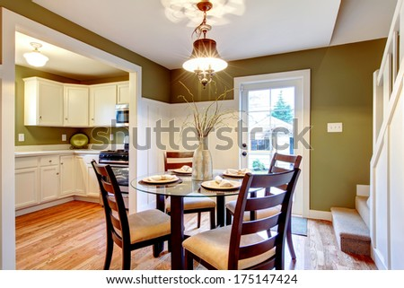 Olive and white dining room with glass table and wood chairs. Silver vase with dry branches and plates accomplish interior design