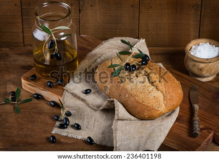 Olive bread, black olives and olive oil on a rustic wooden background - stock photo