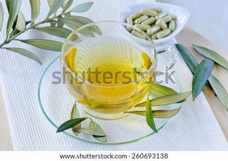 Olive leaf infusion and olive leaf extract capsules. Alternative medicine.  Selective focus. Taken in daylight. - stock photo