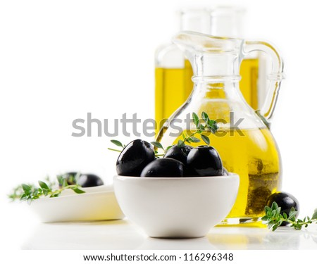 Olive oil and black olives isolated on white - stock photo