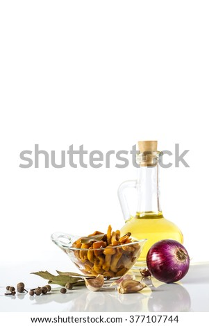 Olive oil and delicious marinated mushrooms in glass bowl, red onion, garlic and spices isolated on white background