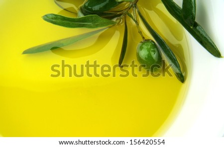 Olive oil and green olive branch in bowl. - stock photo
