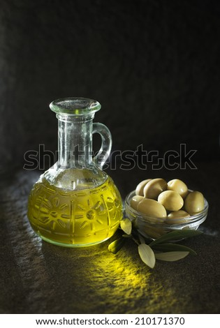 Olive oil and olive branch on the table - stock photo