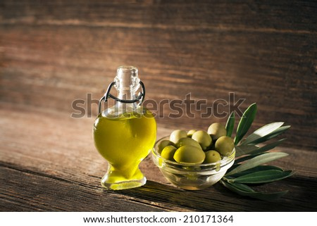 Olive oil and olive branch on the wooden table - stock photo