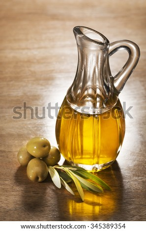 Olive oil and olive branch on the wooden table. - stock photo