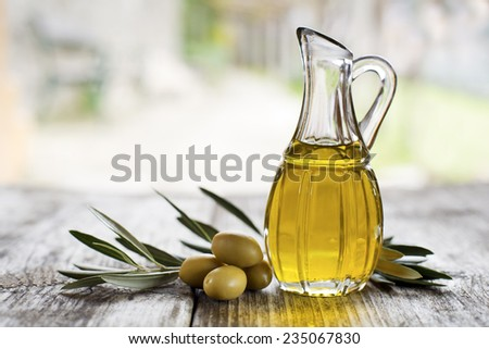 Olive oil and olive branch on the wooden table outside - stock photo