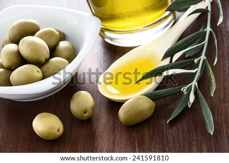 Olive oil and olives branch on the wooden table
