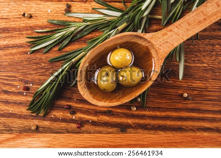 Olive oil and olives in wooden spoon with rosemary and spices, lying on the wooden table - stock photo