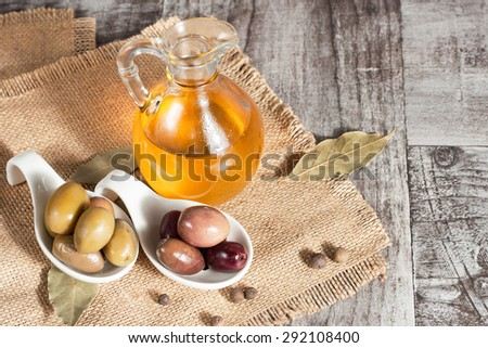 olive oil and olives on a rustic wooden background - stock photo