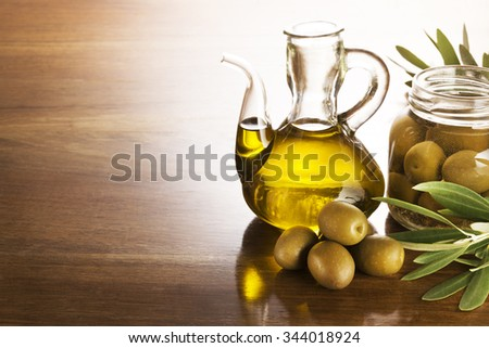 Olive oil and olives on a wooden table. - stock photo