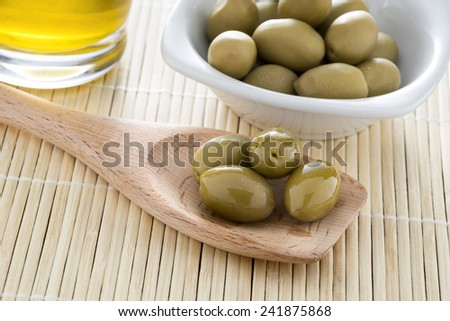 Olive oil and olives on the bamboo table - stock photo