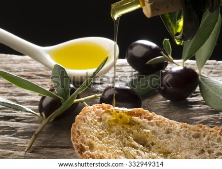 Olive oil and olives on the wooden table - stock photo