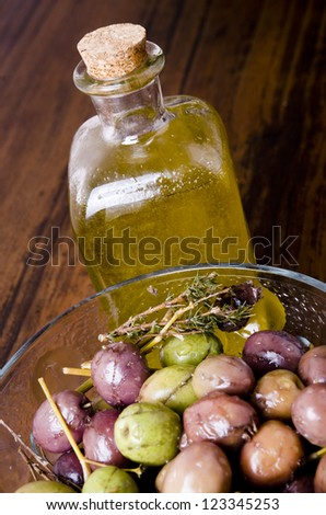 olive oil and olives over wood background
