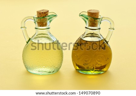 Olive oil and rice wine vinegar in pretty glass jugs on a warm yellow background
