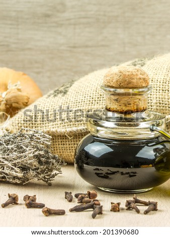Olive oil and vinegar in bottles on old wooden table with thyme, onion, herbs provences - stock photo