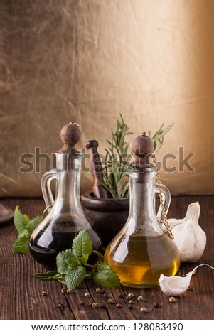Olive oil and vinegar in vintage bottles on old wooden table with garlic, mint and rosemary in vintage mortar - stock photo