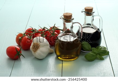 Olive oil and vinegar in vintage bottles on wooden table, cherry tomatoes with garlic - stock photo