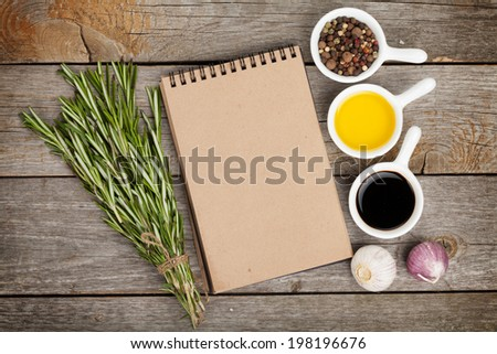 Olive oil and vinegar with spices over wooden table background and notepad for copy space