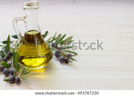 Olive oil bottle framed by branches of the olive tree on a light white wooden background. Bottle of olive oil isolated. Horizontal. Daylight.