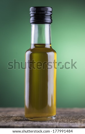 Olive oil  bottle made of glass with a green light spotlight background