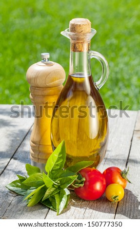 Olive oil bottle, pepper shaker, tomatoes and herbs on wooden table - stock photo