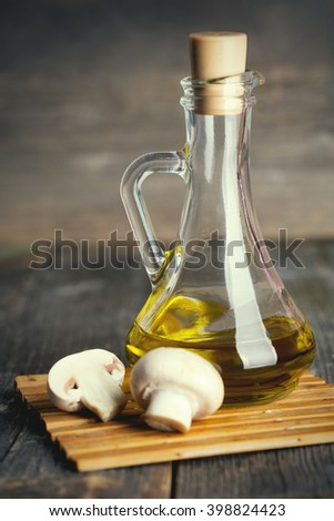 Olive oil bottle with mushroom on wood table