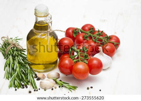 Olive oil, cherry tomatoes, garlic and rosemary on a white wooden background