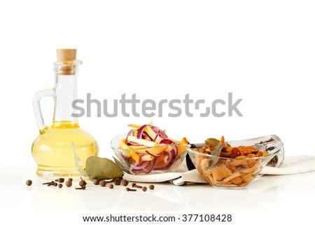 Olive oil, delicious marinated mushrooms and salad with fresh onion and vegetables in glass plate in glass bowls isolated on white background - stock photo
