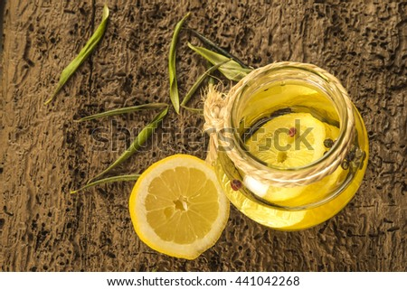 Olive oil flavored with lemon and red peppercorns in glass bottle on old wooden table - stock photo