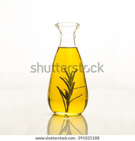 Olive oil flavoured with rosemary in glass bottle isolated on white background. - stock photo