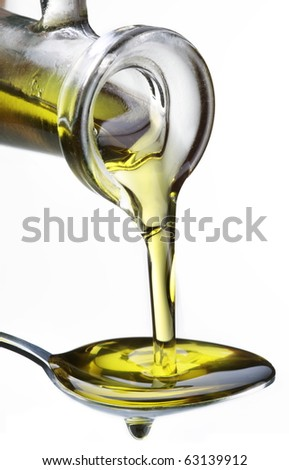 Olive oil flowing from carafe into the spoon isolated on a white. - stock photo