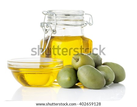 Olive oil in a glass bottle and bowl, olives isolated on a white background closeup
