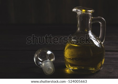 Olive oil in a glass bottle on a dark wooden background. Dark photo in retro style with a homely, rural atmosphere. Space for text