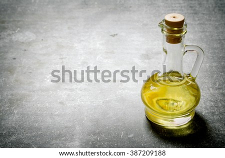 Olive oil in a jug. On a stone background. - stock photo