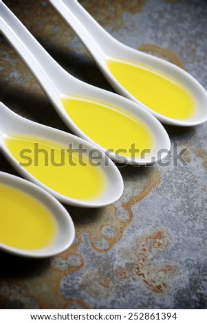 Olive oil in a small china spoons. - stock photo