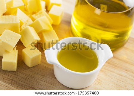 Olive oil in a small glass container with bottle of oil and cubes of butter - stock photo