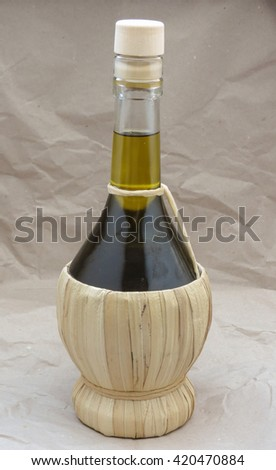 Olive oil in a traditional shaped straw flask - stock photo