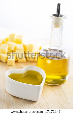 Olive oil in bottle and in a heart with butter in the background - stock photo