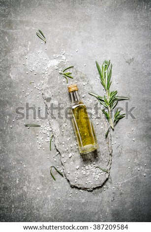 Olive oil in bottle with rosemary and salt. On a stone background. - stock photo