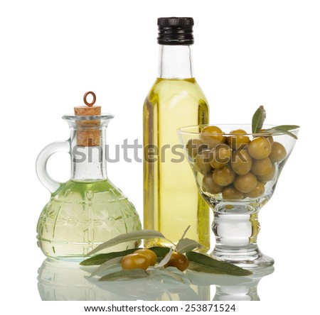 Olive oil in bottles and olivees in glass on white background - stock photo