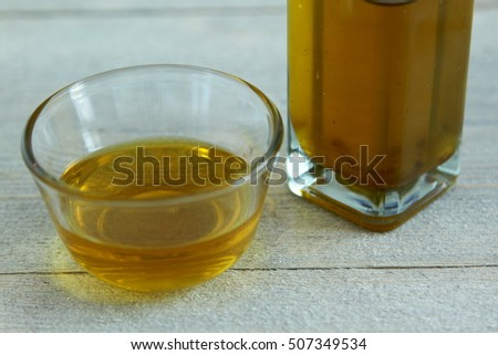 Olive Oil in Glass bowl on wooden background