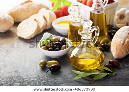 Olive oil in vintage bottles with black and green olives and leaves copyspace on rustic background