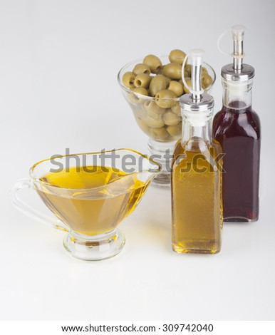 Olive oil, olives and wine vinegar in the bowl of glass on a white background - stock photo