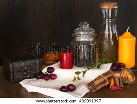 Olive oil, pepper, candle, cinnamon on chopping board