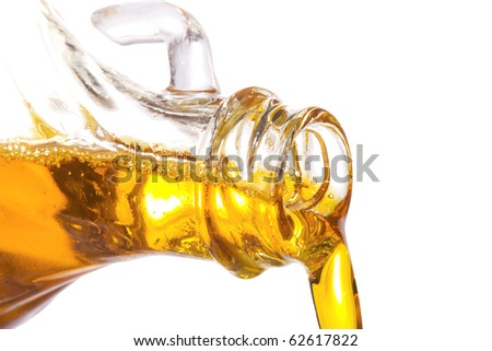 olive oil pouring down from bottle on white background