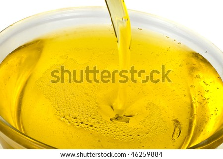 olive oil pouring  in bowl on white background  - stock photo