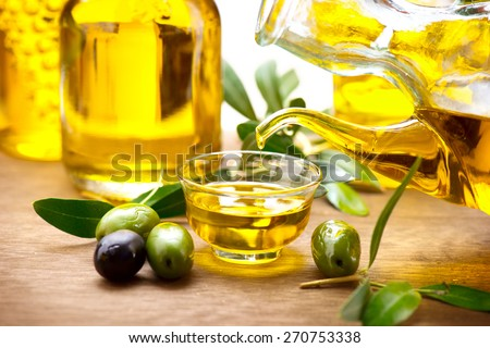 Olive Oil. Pouring Virgin Olive Oil in a bowl close up. Olives and Healthy Olive oil being poured from glass bottle. Diet. Bottle of olive oil. Dieting concept. Healthy food - stock photo