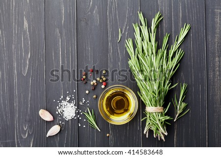 Olive oil, rosemary plant, salt, garlic and pepper on black table from above for food cooking background or menu  - stock photo