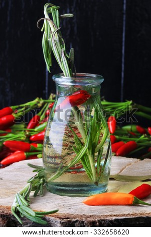 olive oil spiced with hot pepper rosemary on a black wooden background - stock photo