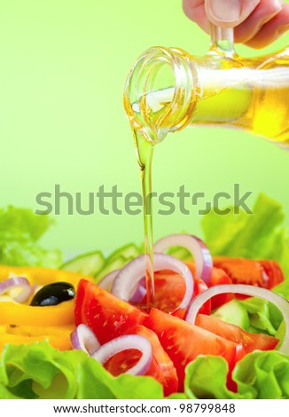olive oil stream and healthy fresh vegetable salad - stock photo